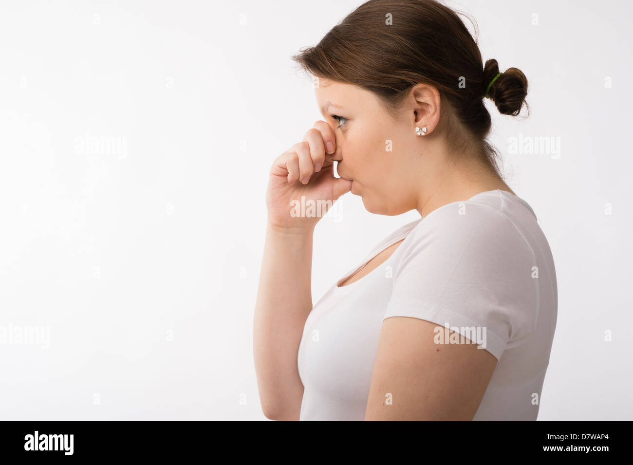 A young brunette teenage Caucasian girl sucking her thumb immature moody sulky sulking adolescent uk - Stock Image