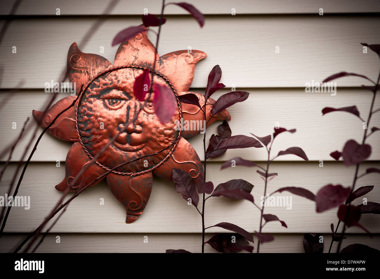 A smiling metal sun face ornament hanging on a wall. Stock Photo