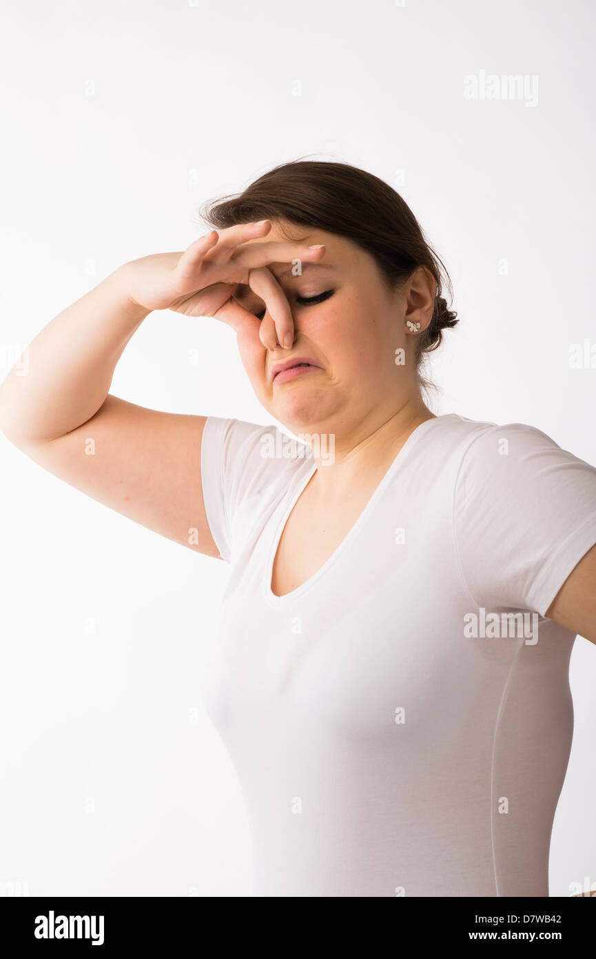 A young brunette teenage Caucasian girl pinching holding her nose to keep out a bad smell odour - Stock Image