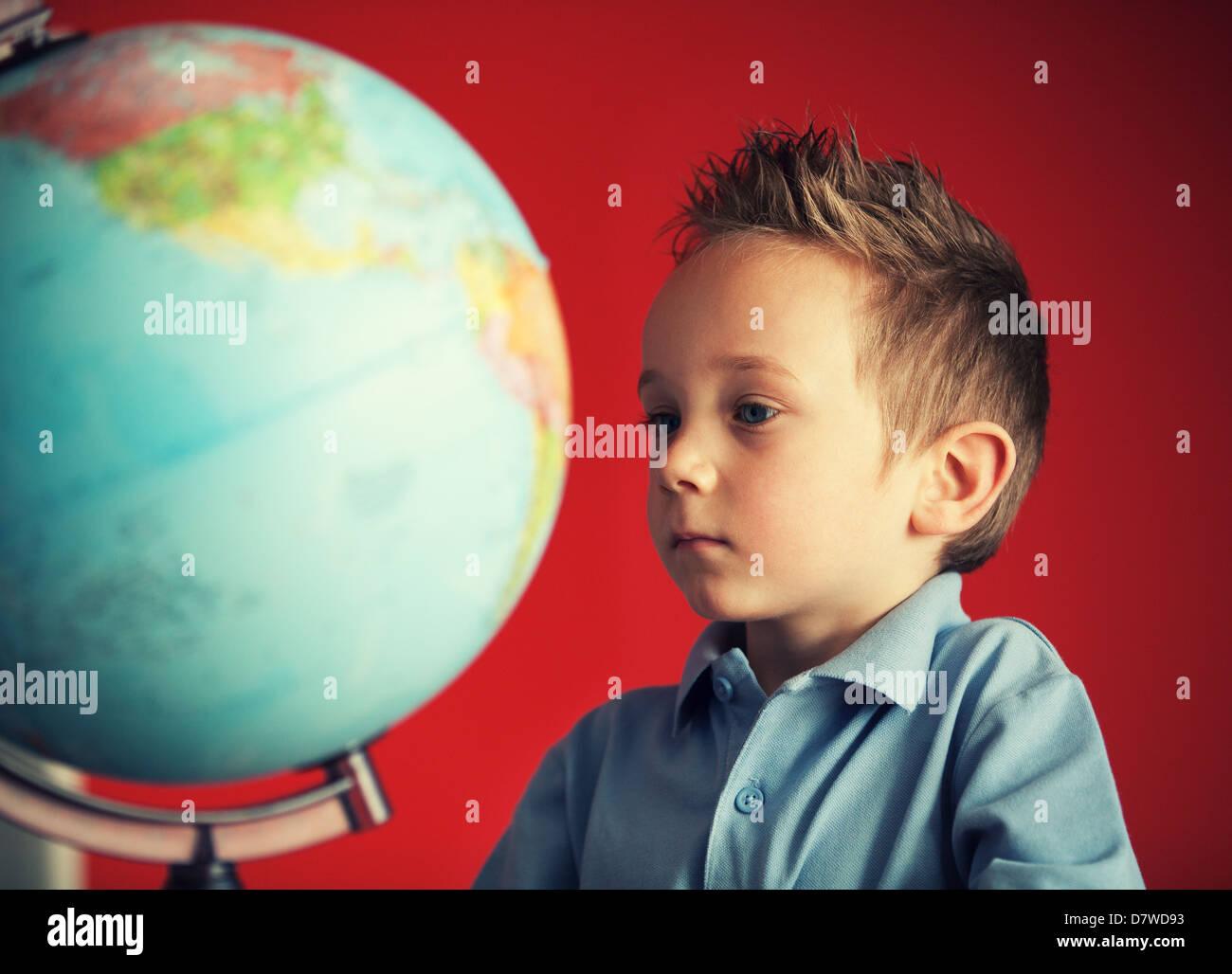 school boy looking at globe Stock Photo