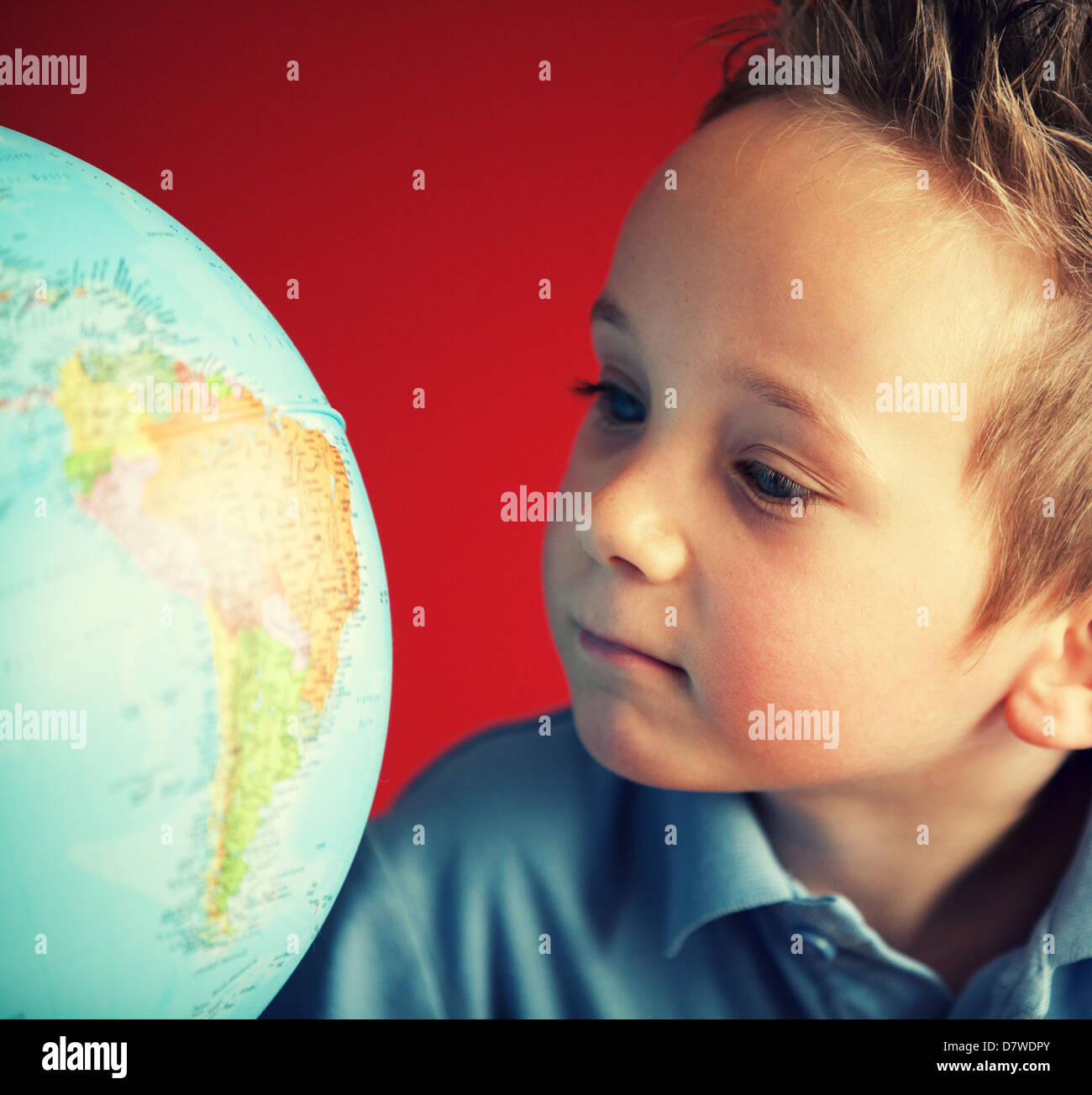 school boy looking at globe - Stock Image