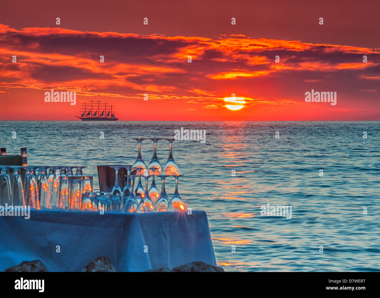 Red sunset with a Pirate ship on the distant horizon - Stock Image
