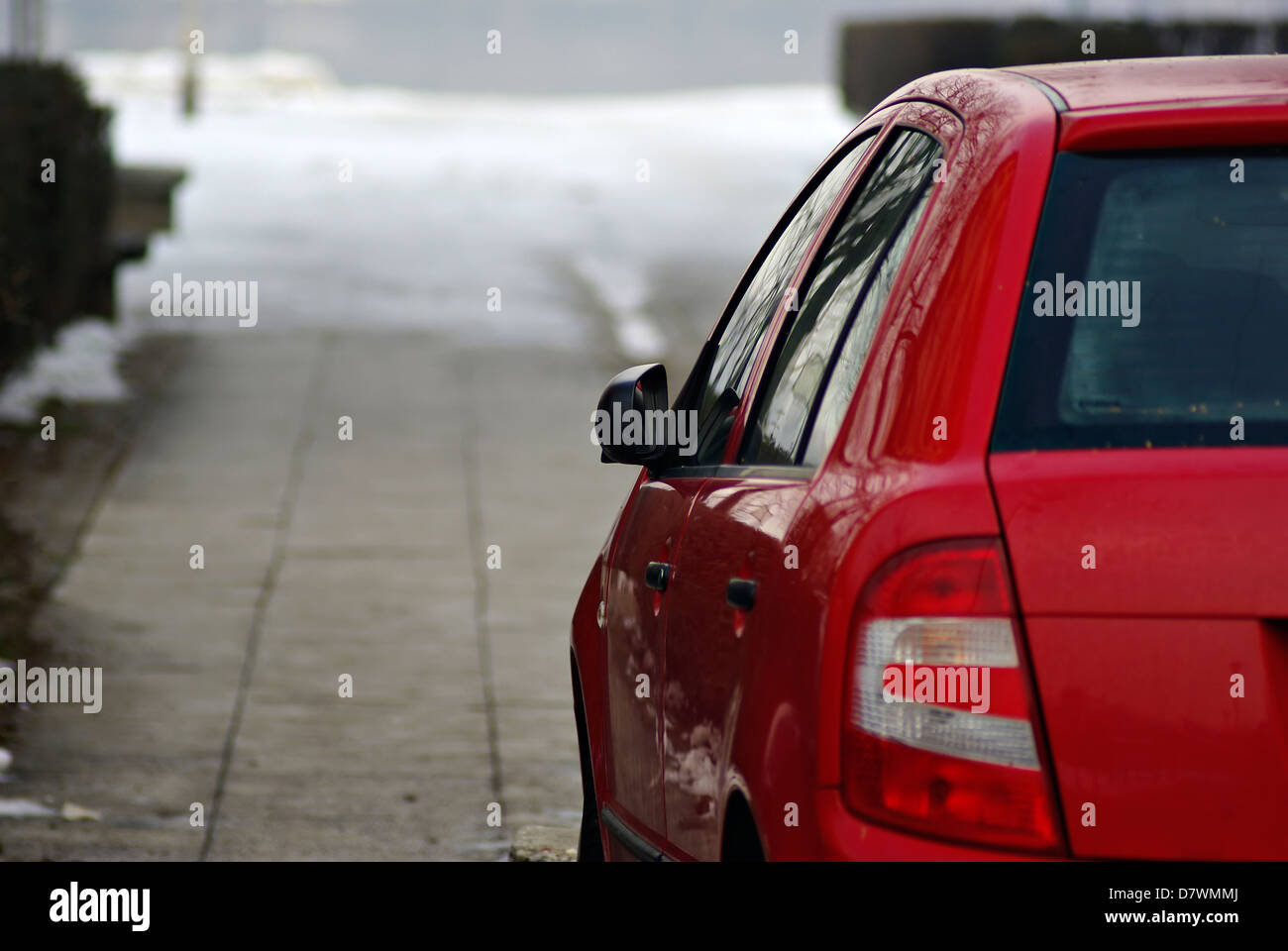 Rear part of red passenger car with blurred background. - Stock Image