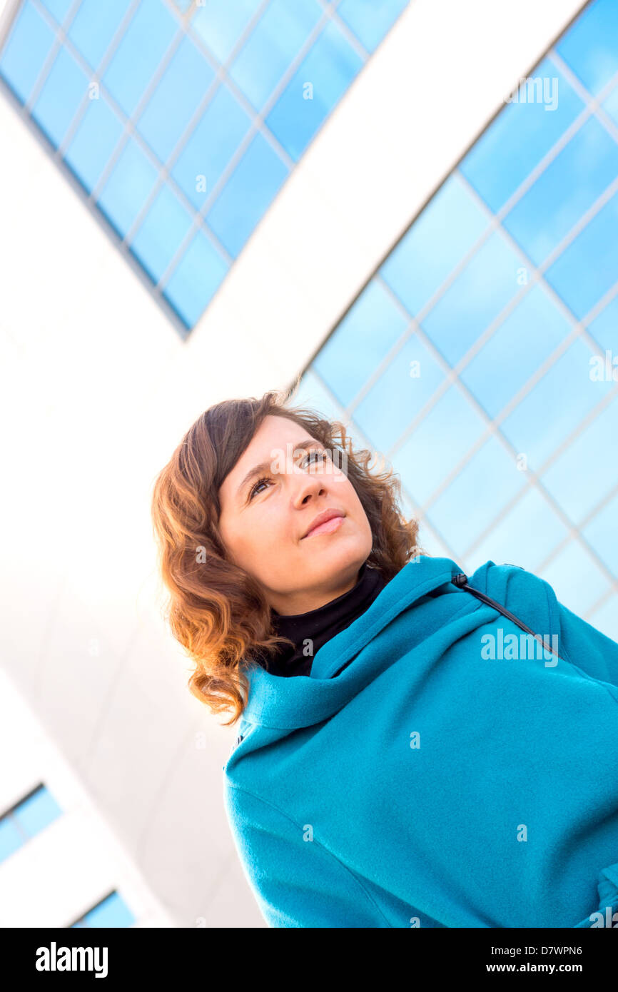 Smiling brunette beautiful business woman wearing blue suit outside portrait over glass wall (building). Vertical, - Stock Image