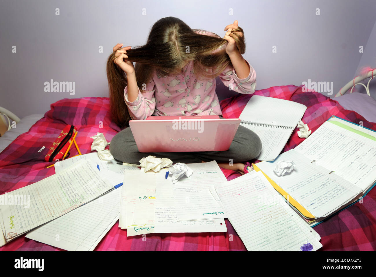 A stressed teenager revising for her exams. - Stock Image