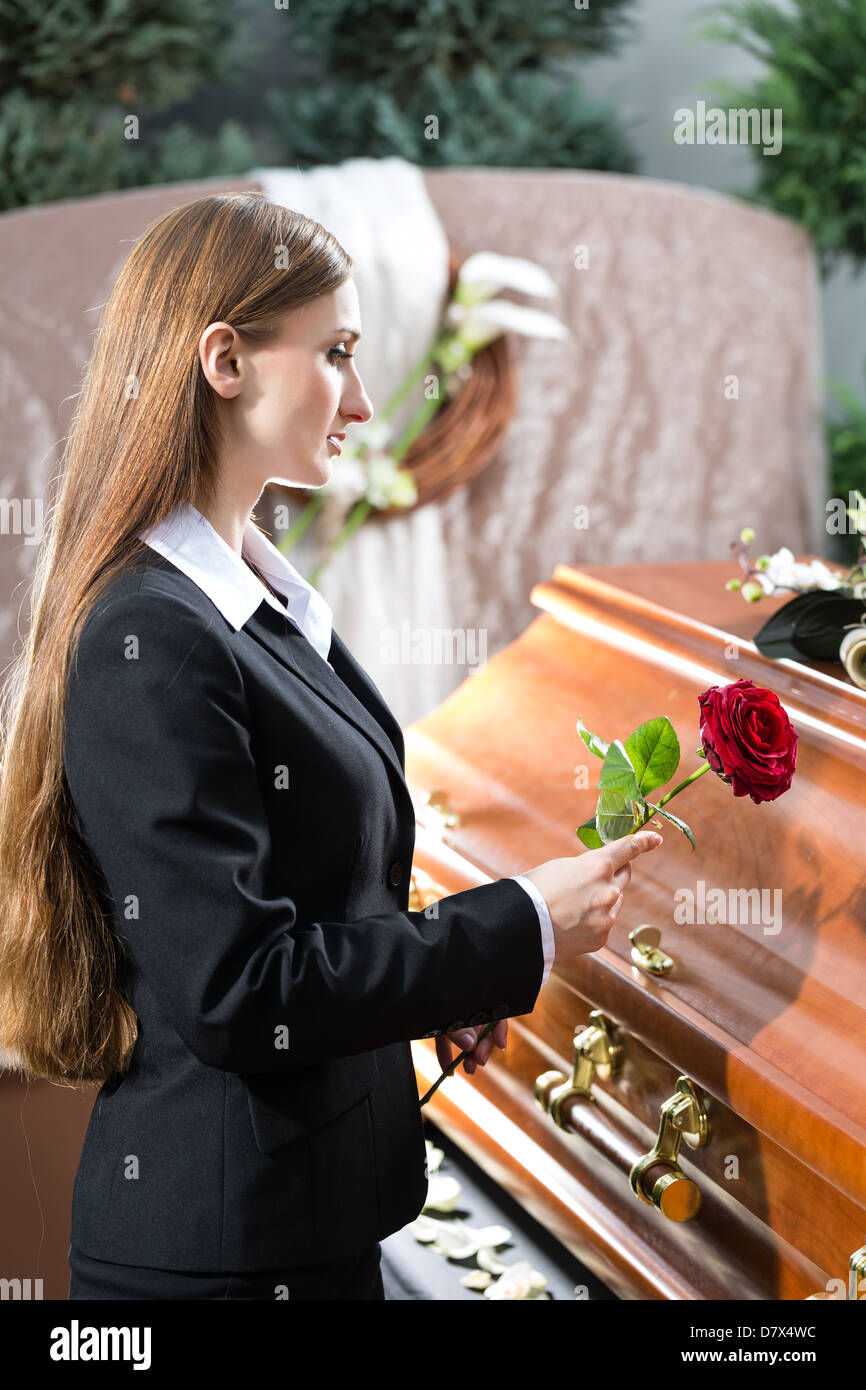 Mourning woman on funeral with red rose standing at casket or coffin - Stock Image