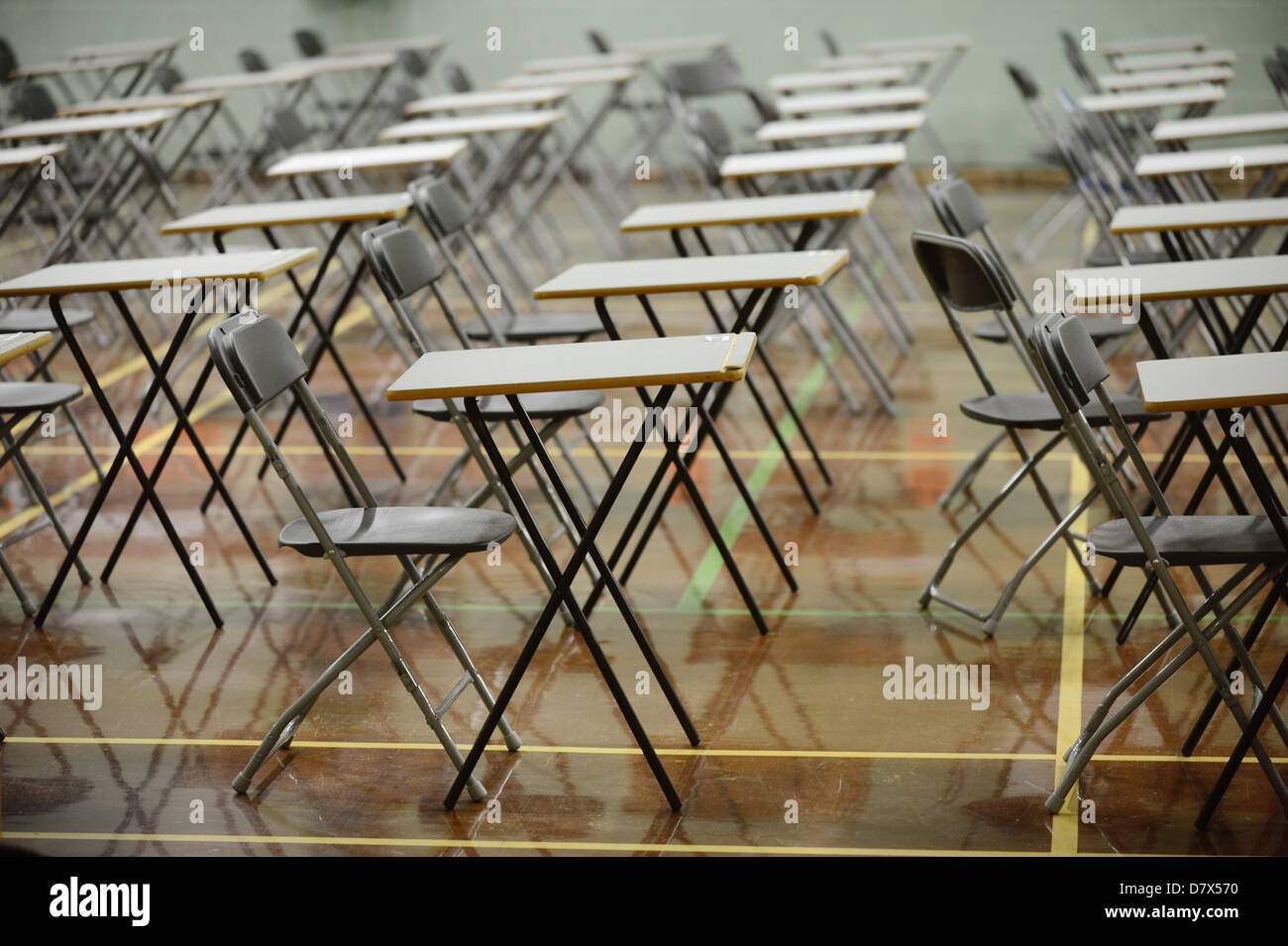 desks set out in a school hall in preparation for exam empty tables - Stock Image