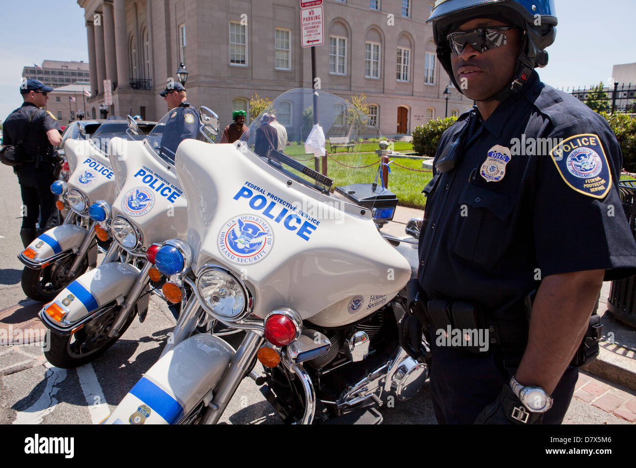 US Department of Homeland Security Federal Protective Service Police officer standing next to service motorcycle - Stock Image