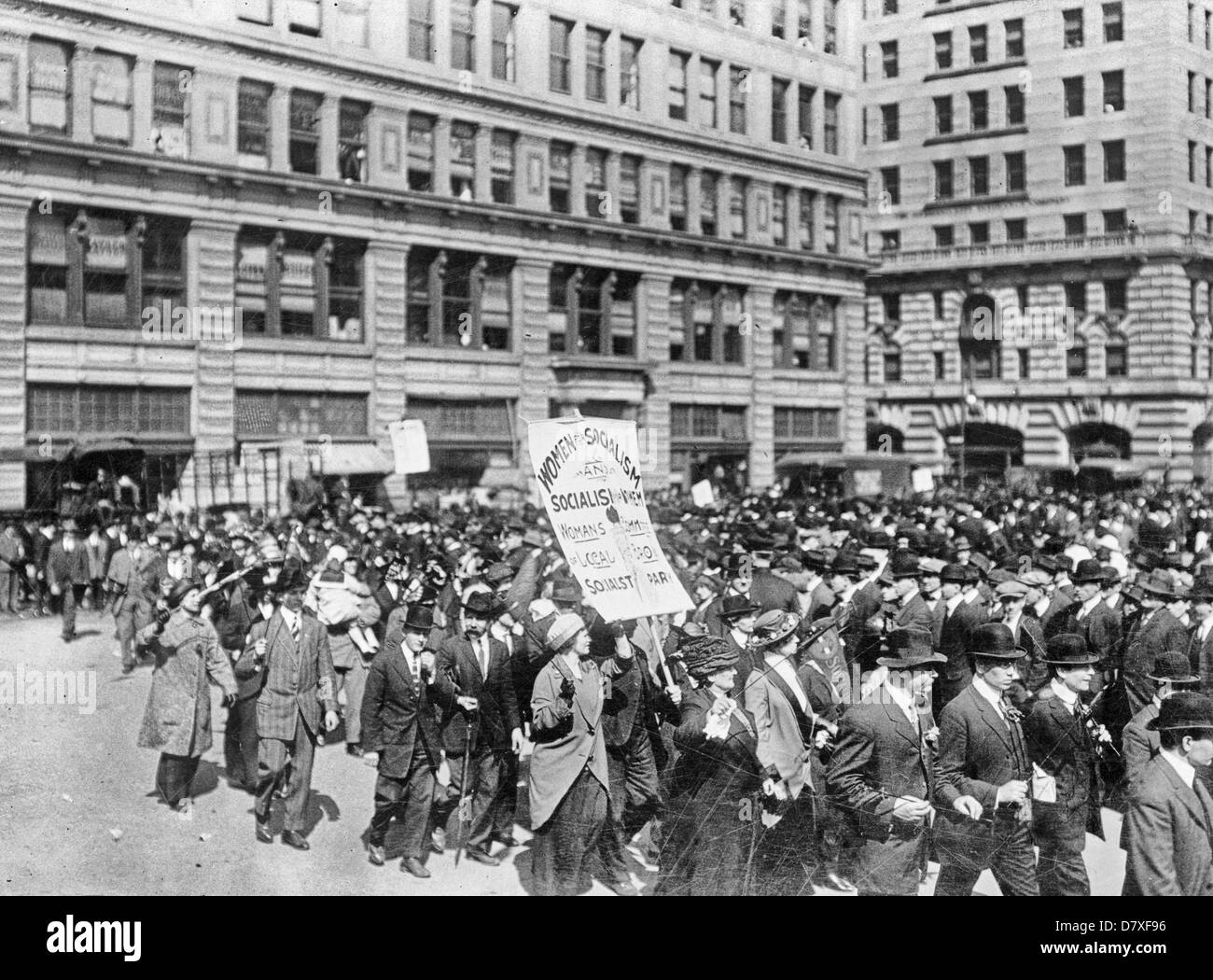 Large group of people walking in the street; one woman is carrying a placard, 'Women for Socialism and Socialism - Stock Image