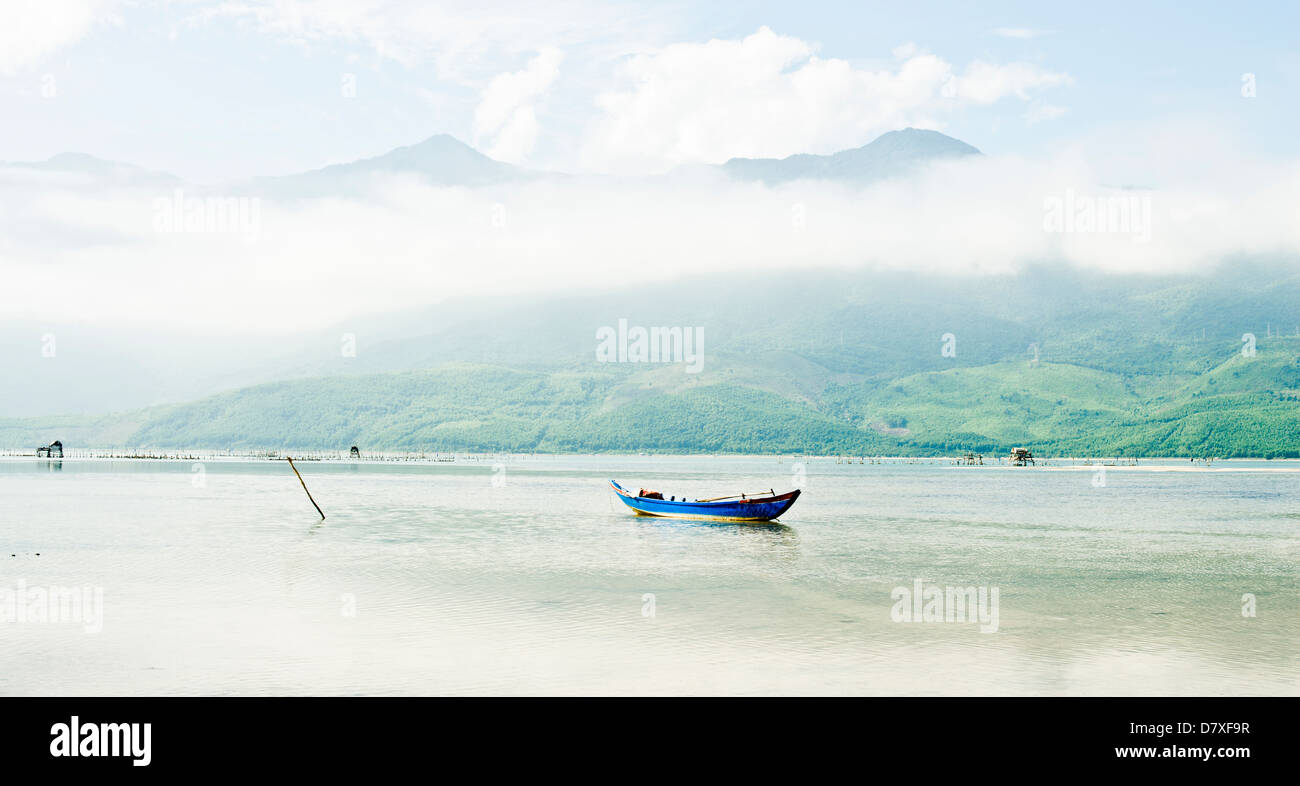A fishing boat in the middle of a large lake near Hue, Vietnam - Stock Image