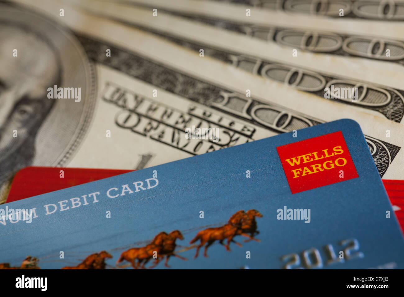 Wells Fargo debit card on $100 bills - Stock Image