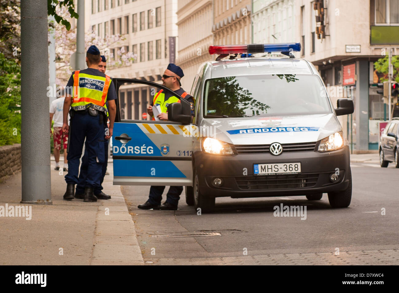 Budapest , Hungary , white blue Rendorseg VW police car 3 three policemen cops stand chatting on pavement - Stock Image