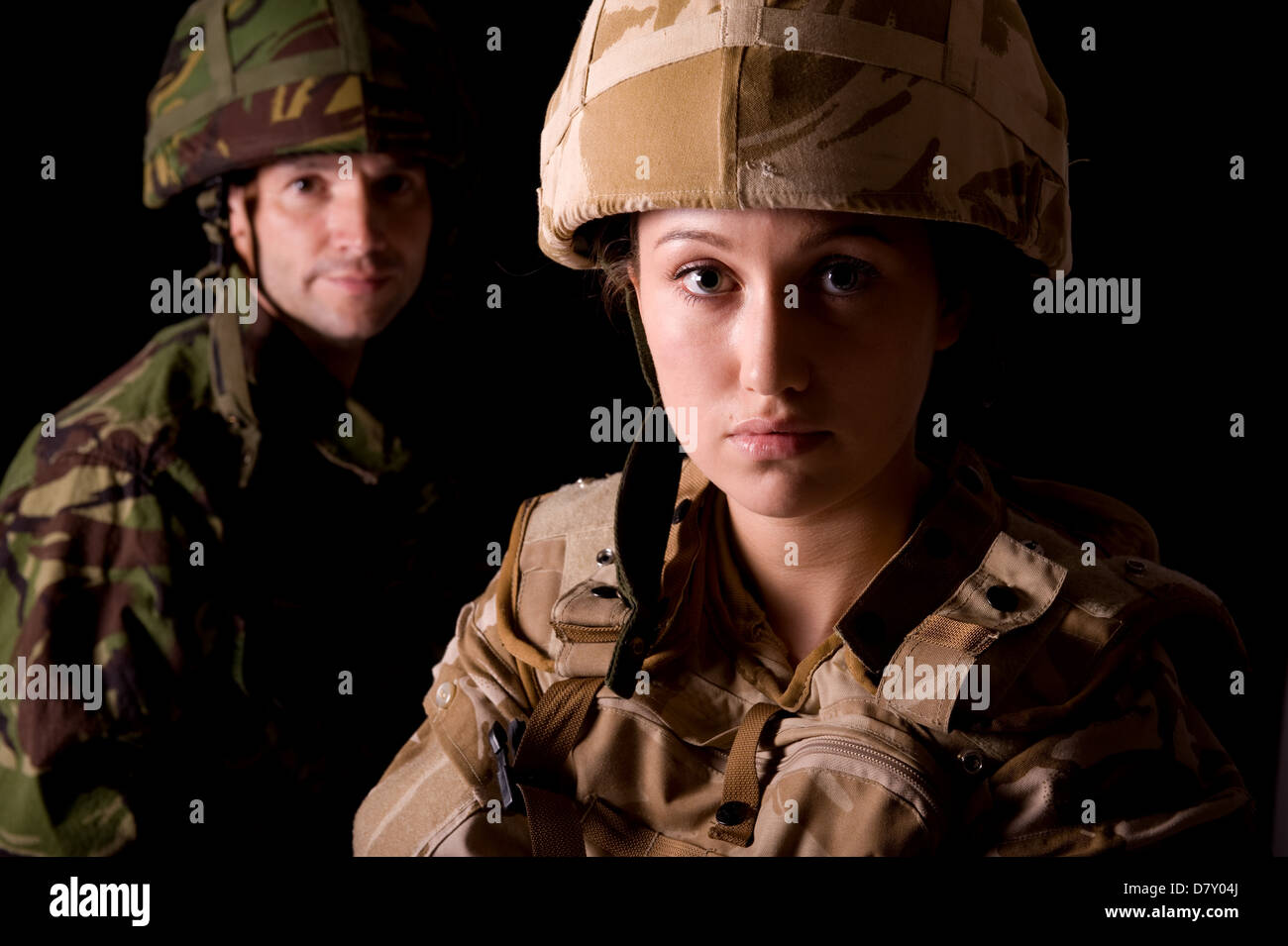 Female soldier in British Military desert uniform in foreground & male soldier in green camouflage uniform in the Stock Photo
