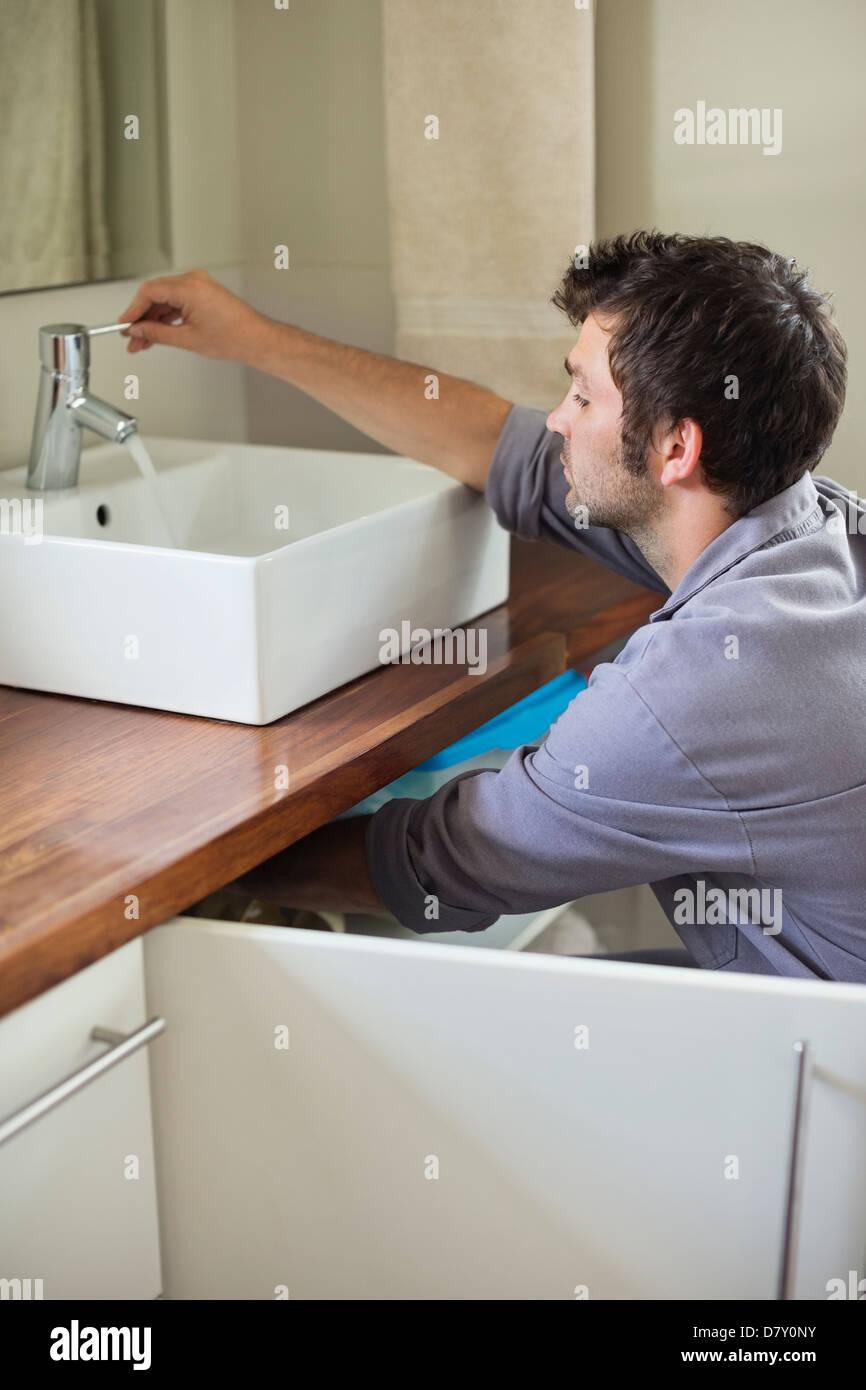 Plumber working on bathroom sink - Stock Image