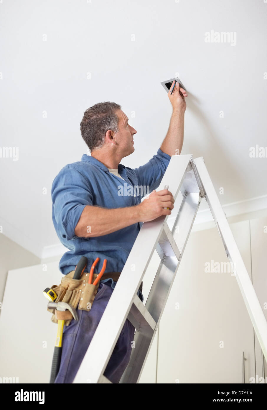 Electrician working on ceiling lights - Stock Image