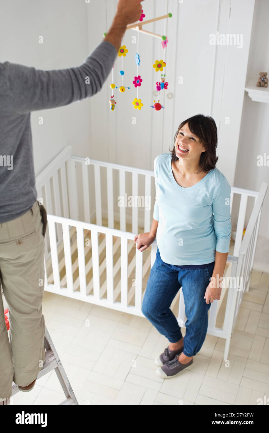 Couple decorating new baby's room - Stock Image