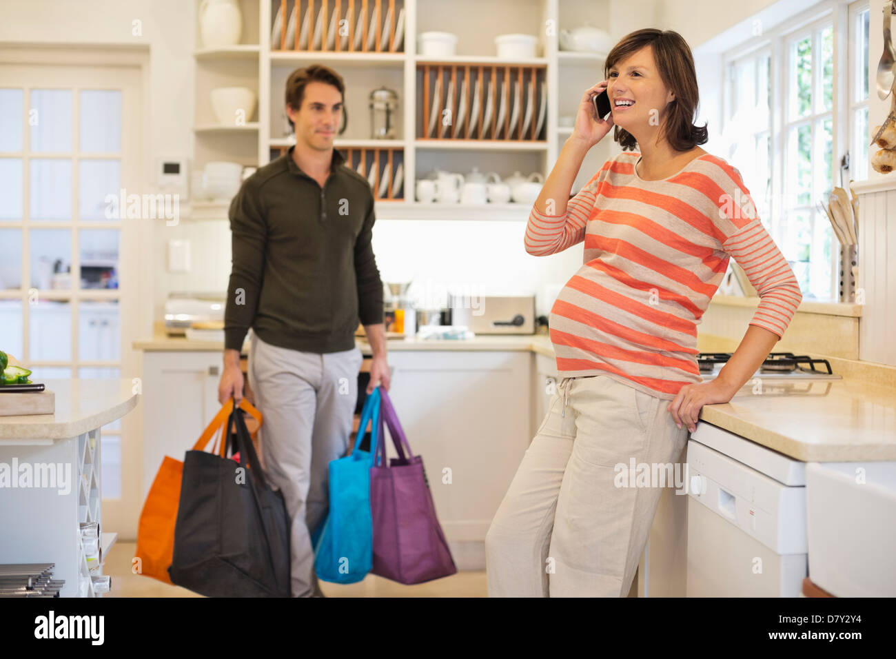 Man carrying bags for pregnant girlfriend - Stock Image