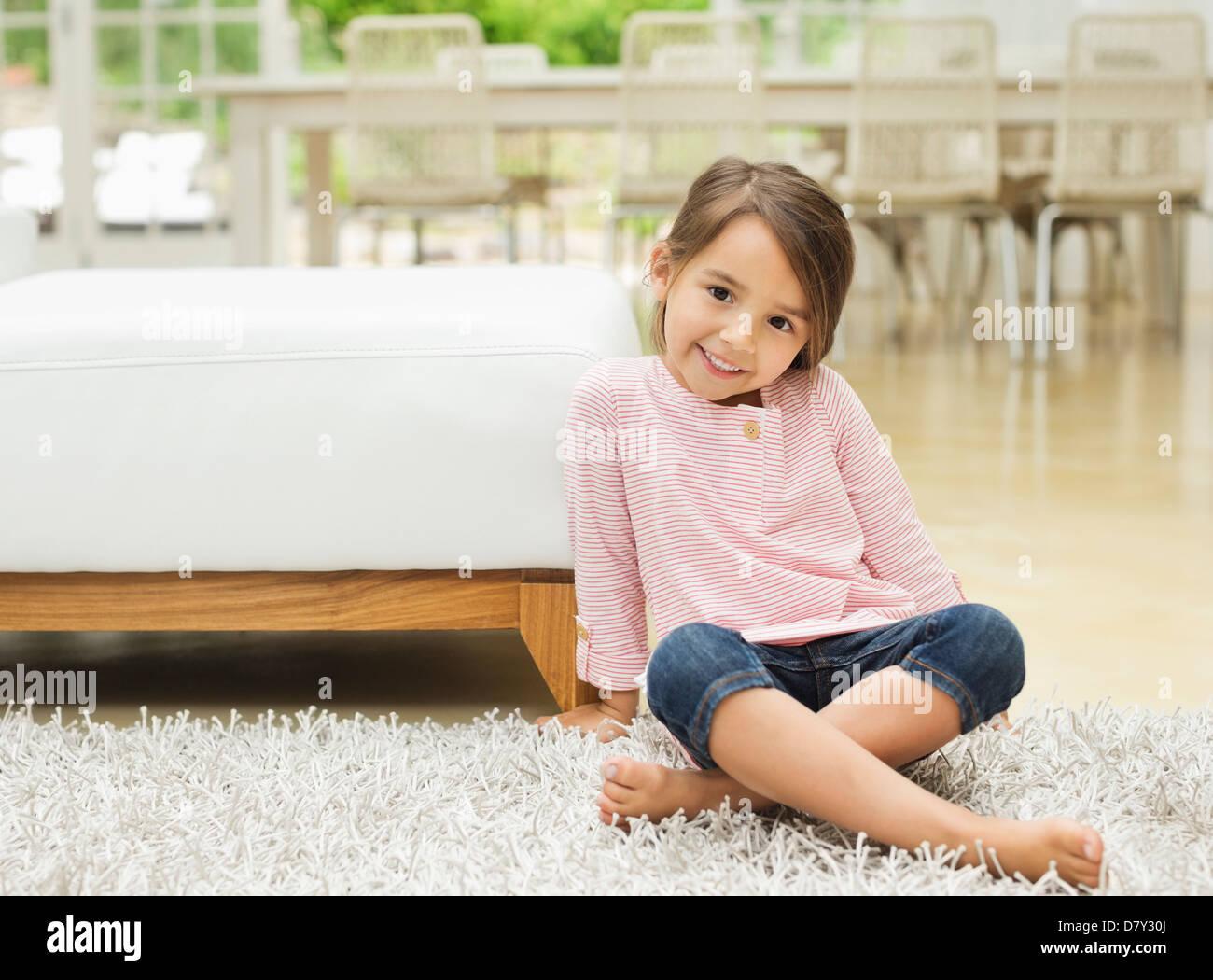 Smiling girl sitting on rug - Stock Image