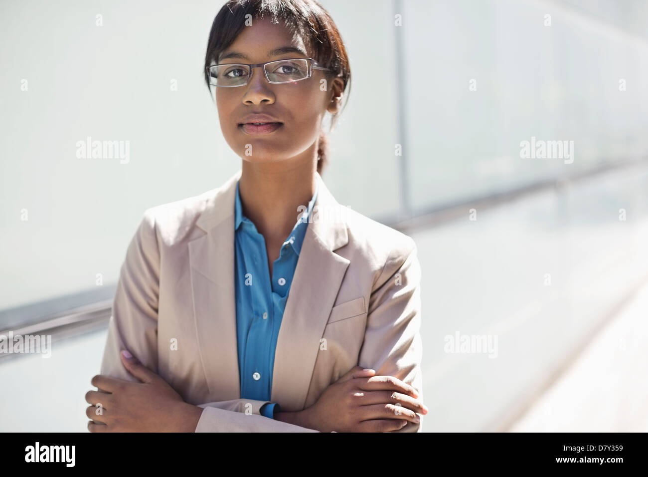 Businesswoman standing with arms crossed - Stock Image