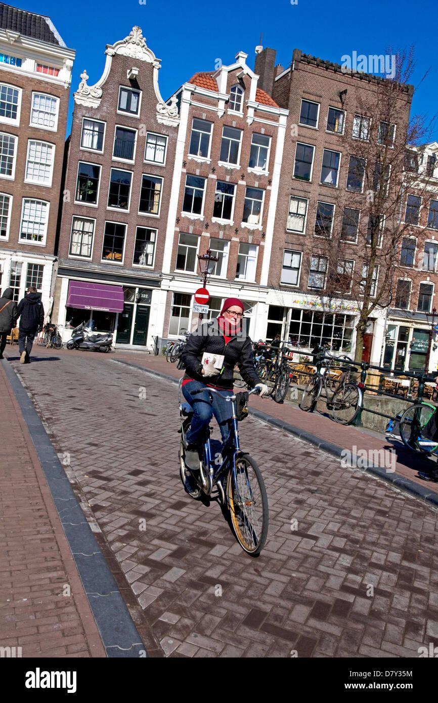 Cyclist on bridge over Prinsengracht canal Grachtengordel-west, Jordaan, central Amsterdam, Netherlands - Stock Image