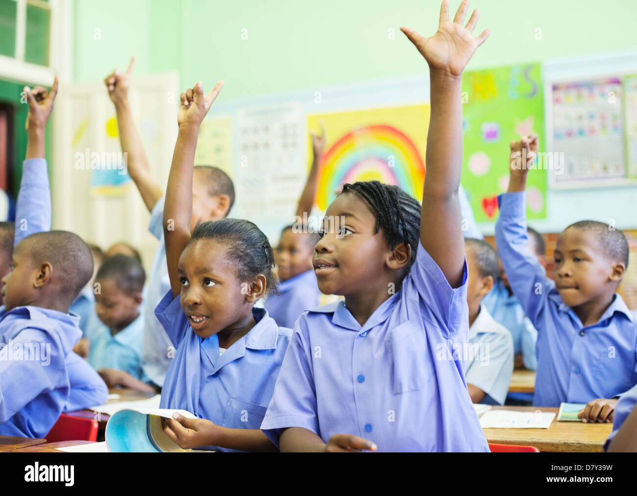 Students raising hands in class - Stock Image