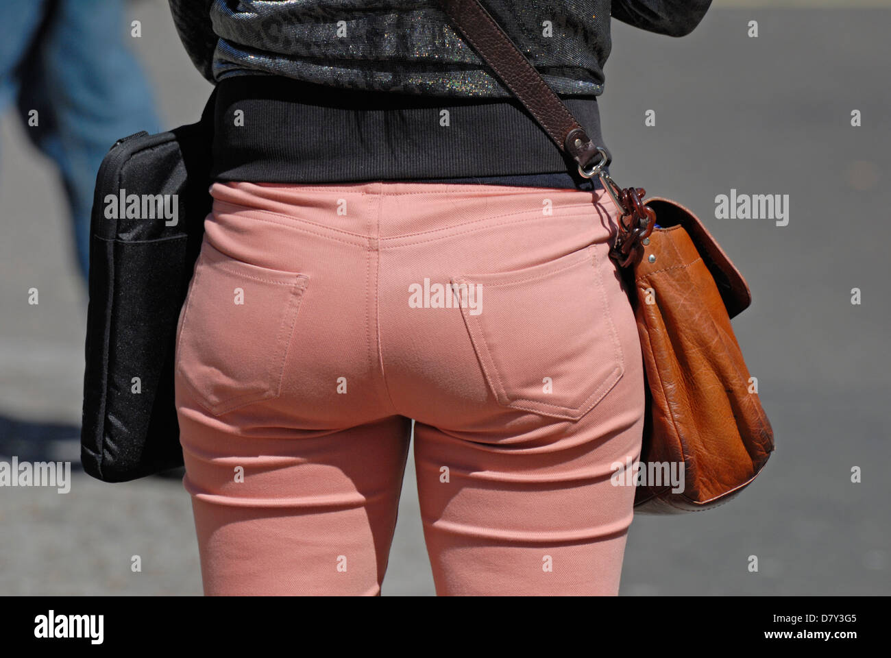 London, England, UK. Woman wearing tight, pink, creased jeans and carrying leather bag - Stock Image