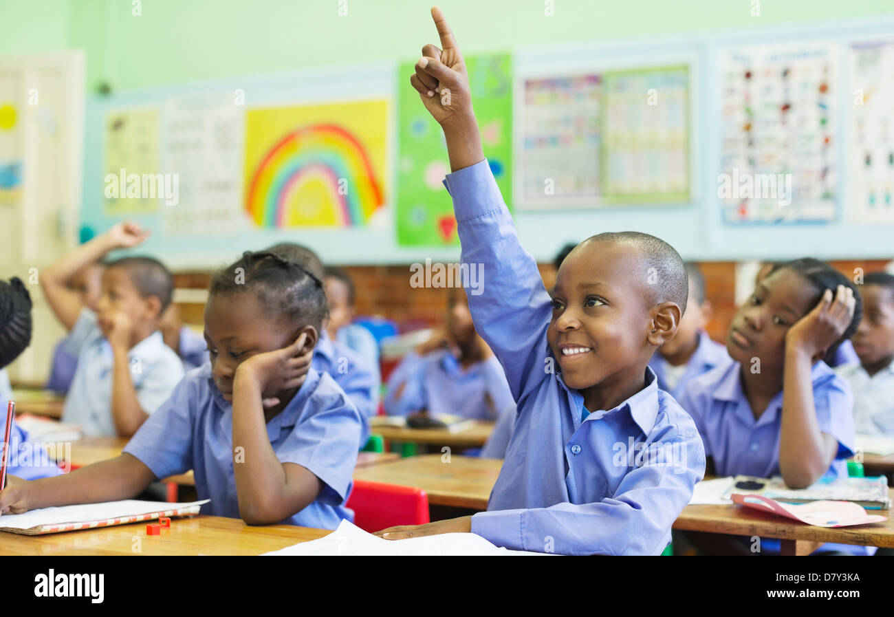 Student raising hand in class - Stock Image