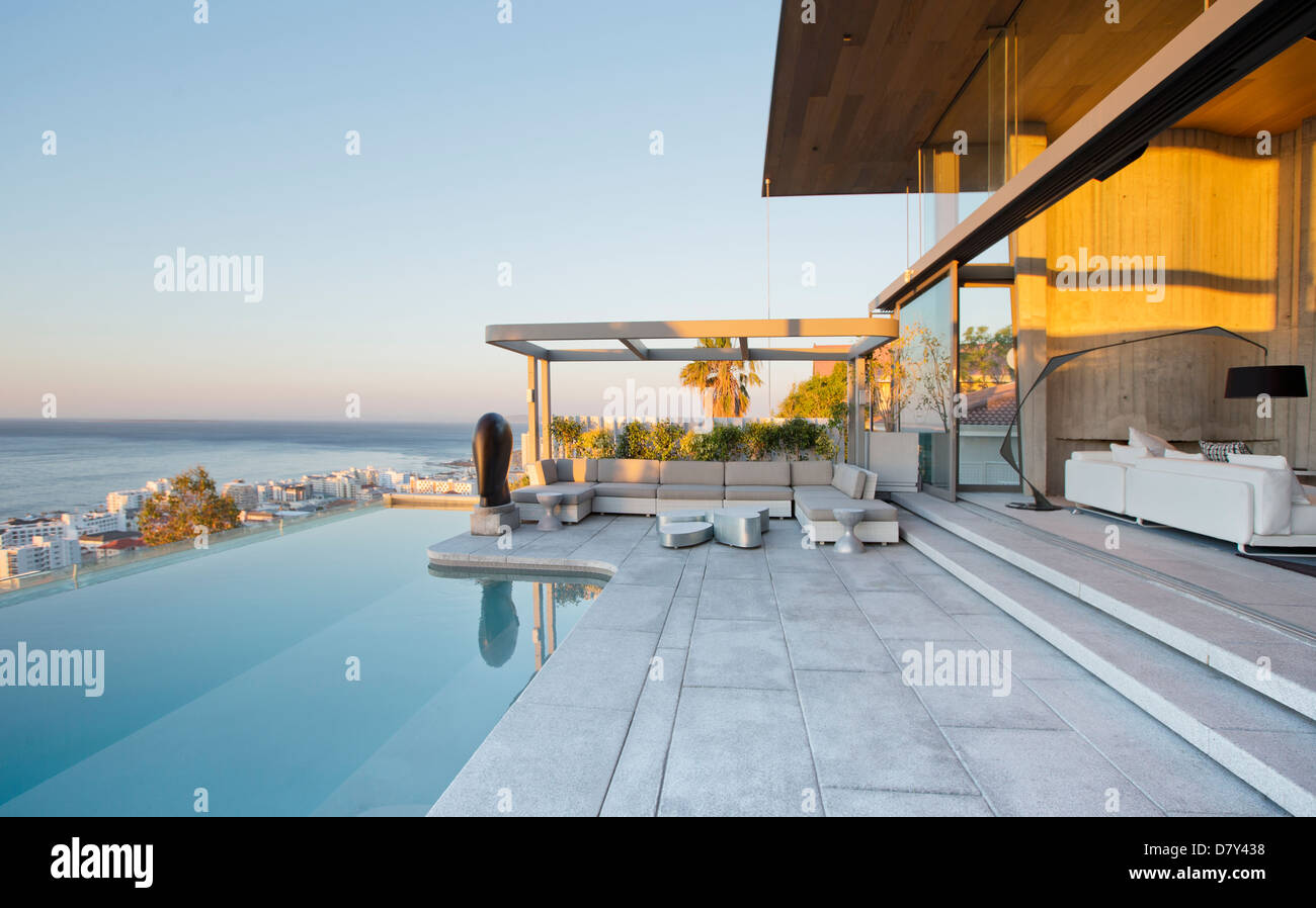 Infinity pool and patio of modern house - Stock Image