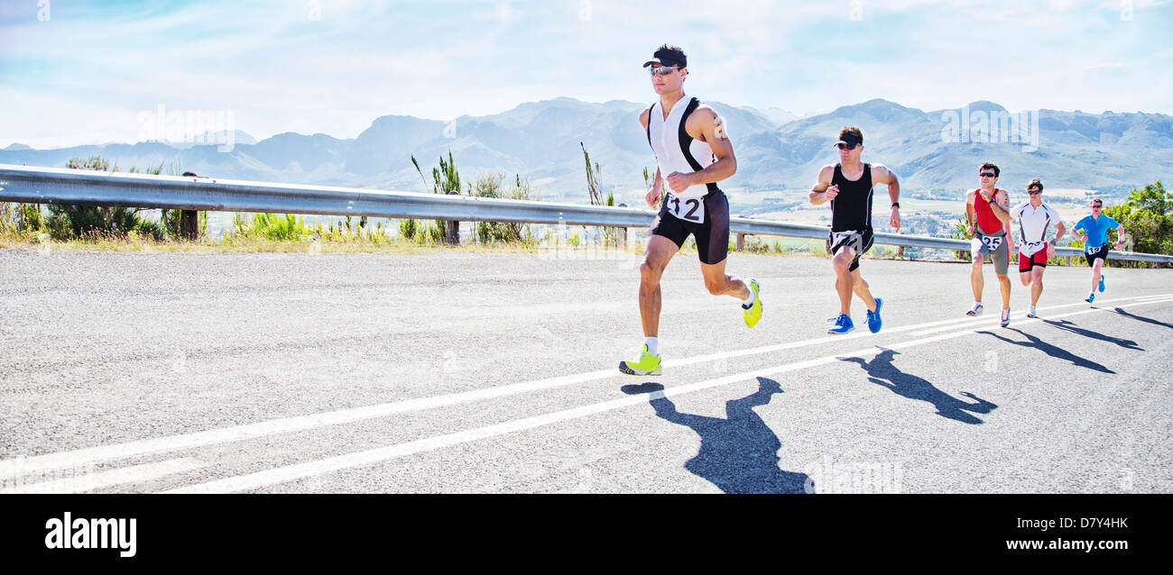 Runners in race on rural road - Stock Image