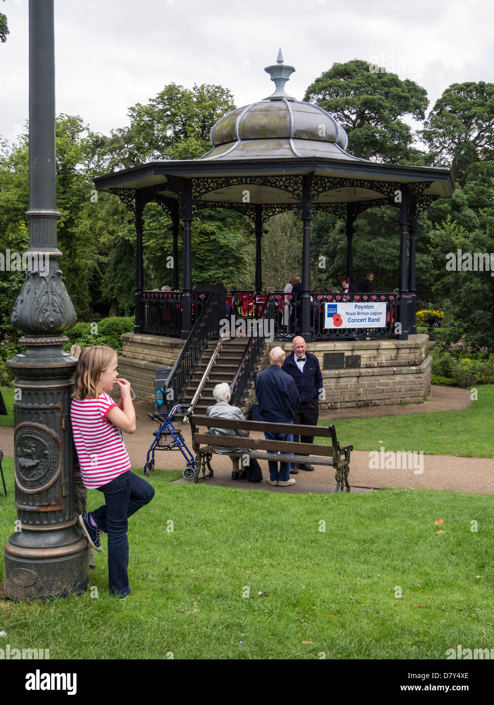 Young child /girl leaning against a lamp post with elderly people and Buxtons bandstand  in background Derbyshire - Stock Image