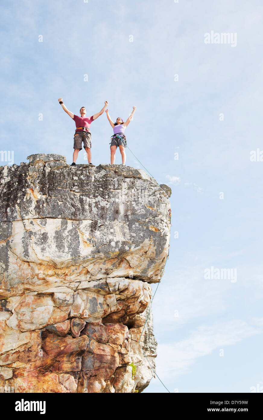 Climbers cheering on rocky cliff Stock Photo