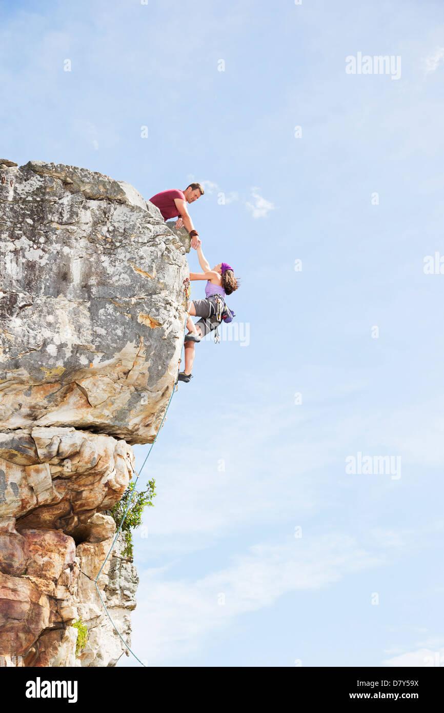 Climbers scaling steep rock face - Stock Image