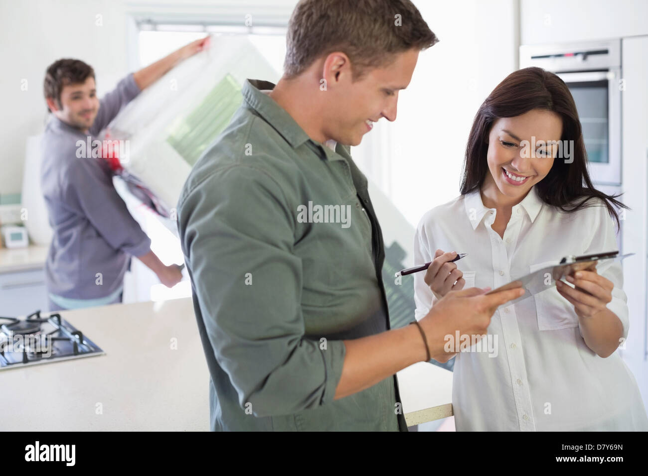 Woman signing for delivery in kitchen - Stock Image