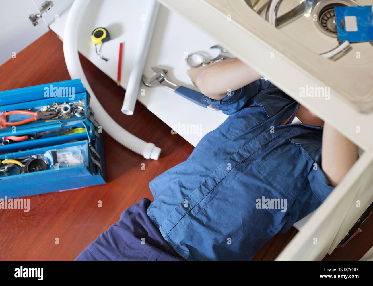 Plumber working on pipes under sink - Stock Image