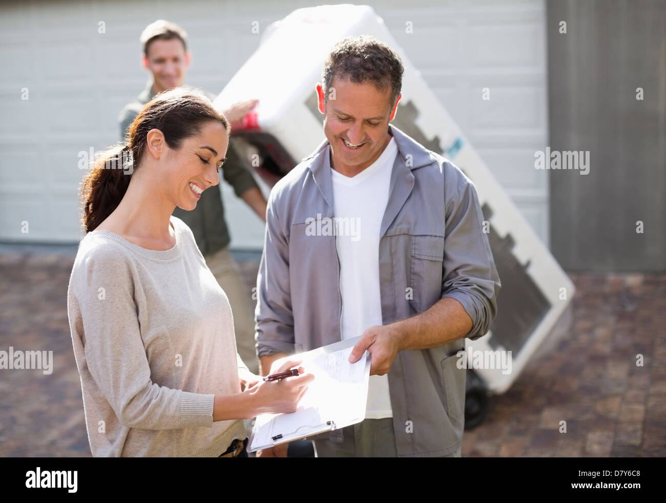 Woman signing for delivery in driveway - Stock Image