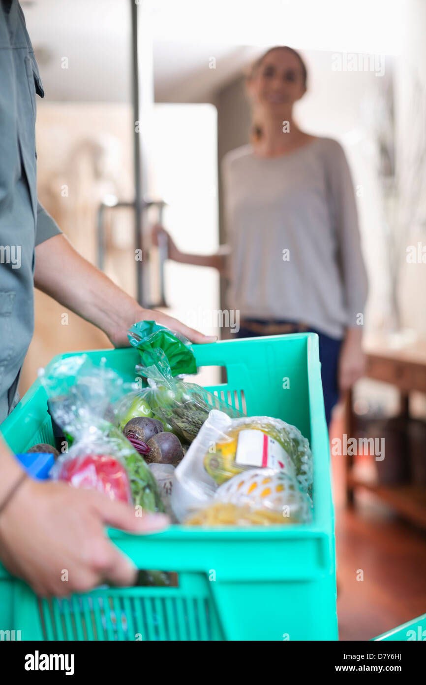 Woman receiving delivery at front door - Stock Image