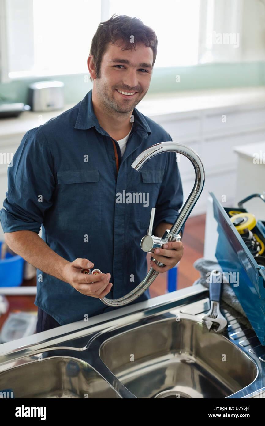 Plumber working on kitchen sink - Stock Image