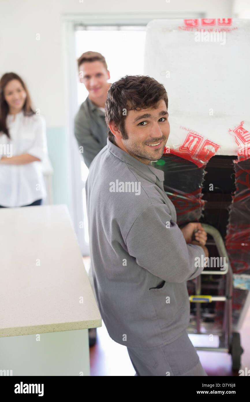 Worker wheeling appliance in kitchen - Stock Image