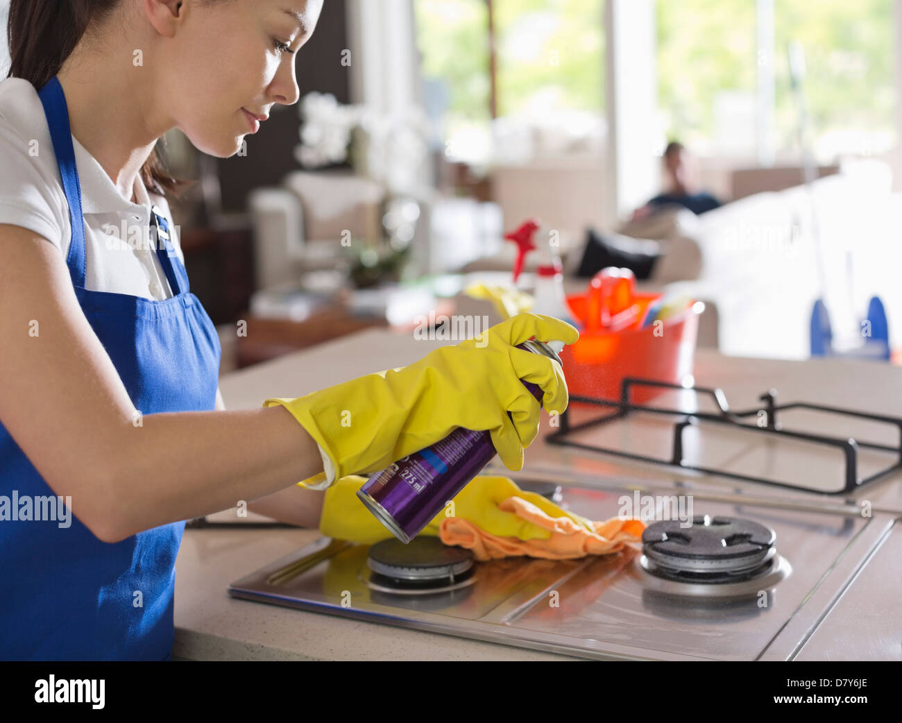 Maid cleaning stove top - Stock Image