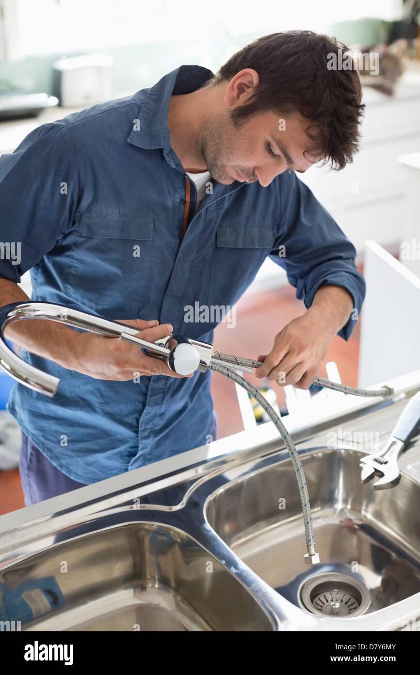 Plumber working on kitchen sink Stock Photo