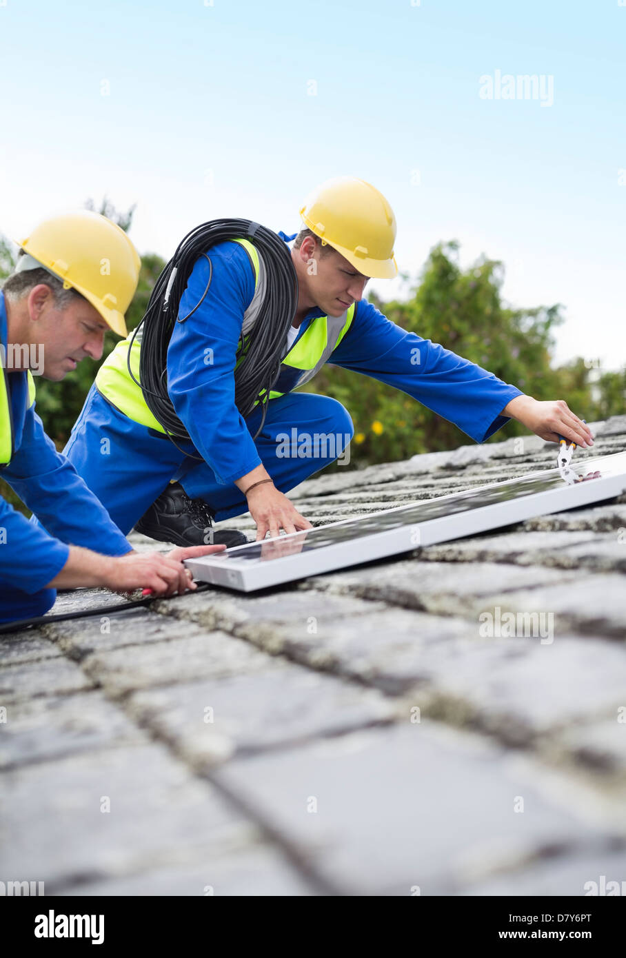 Workers installing solar panels on roof - Stock Image
