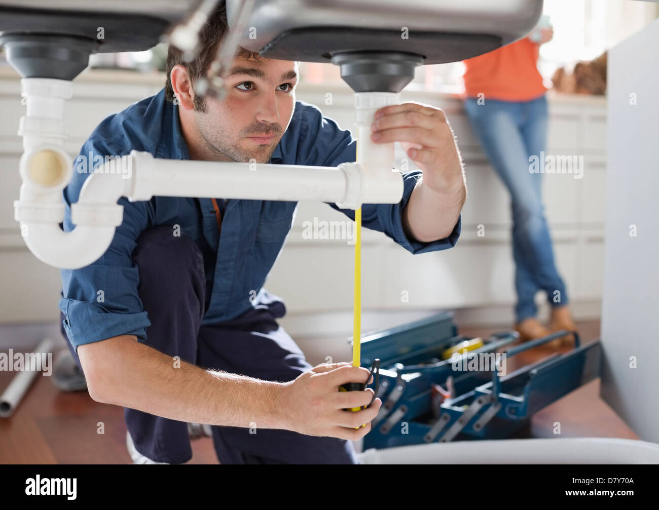 Plumber working on pipes under kitchen sink - Stock Image