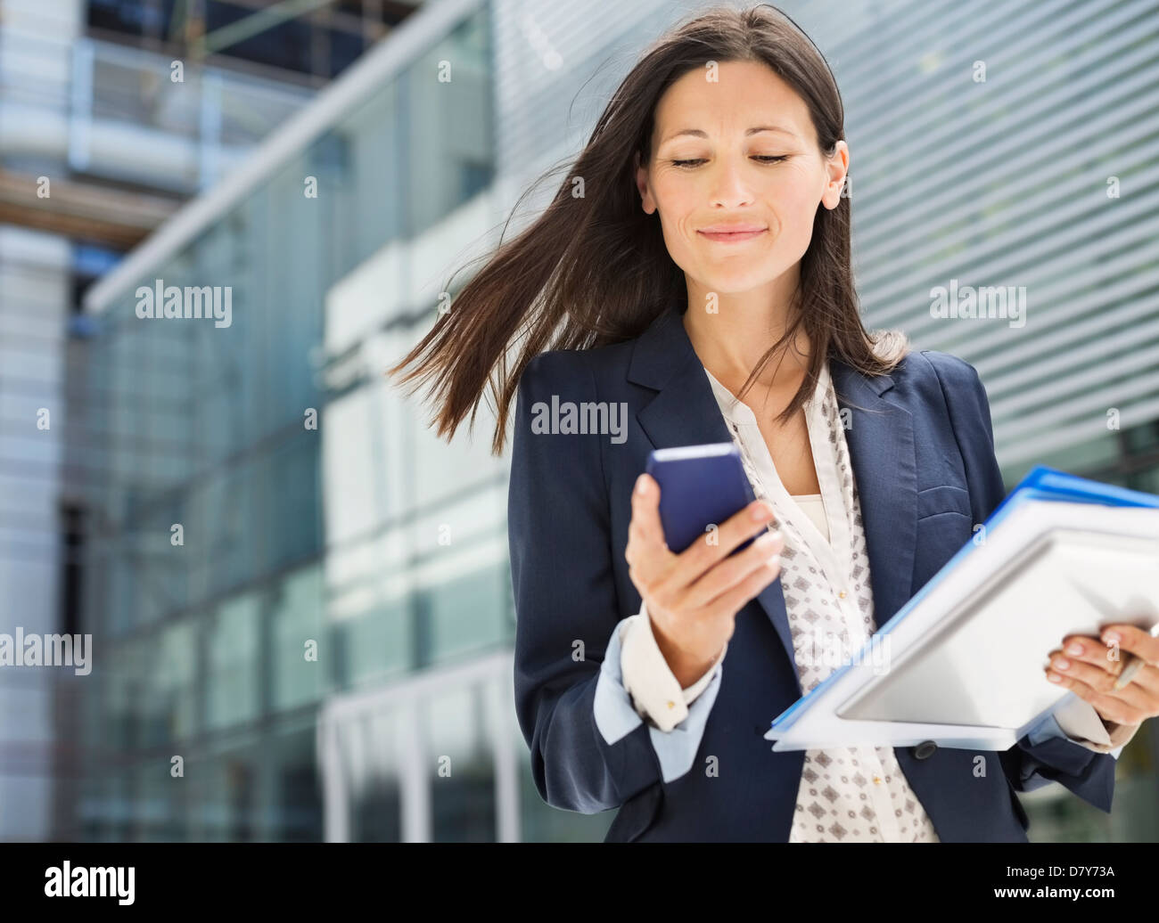 Businesswoman using cell phone in office - Stock Image