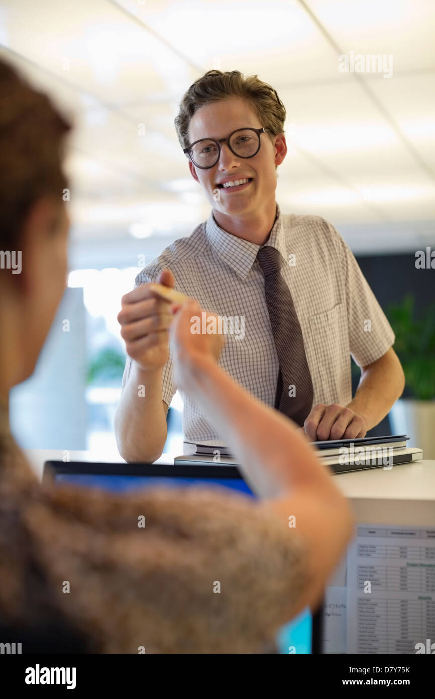Business people exchanging cards in office - Stock Image