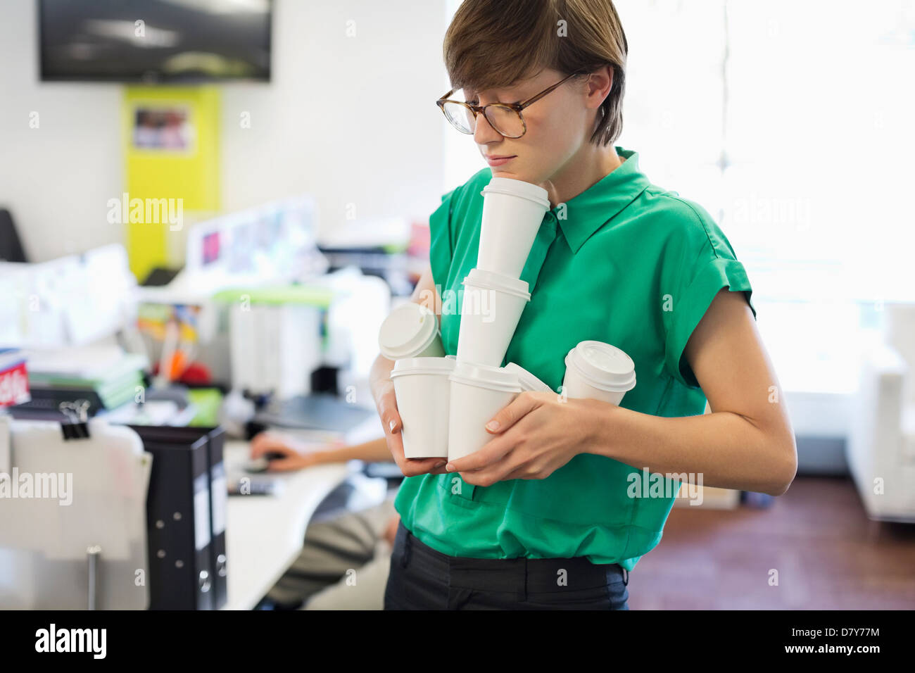 Businesswoman balancing empty coffee cups - Stock Image