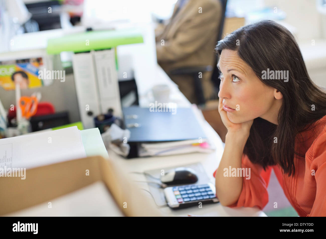 Businesswoman resting chin in hand on desk - Stock Image