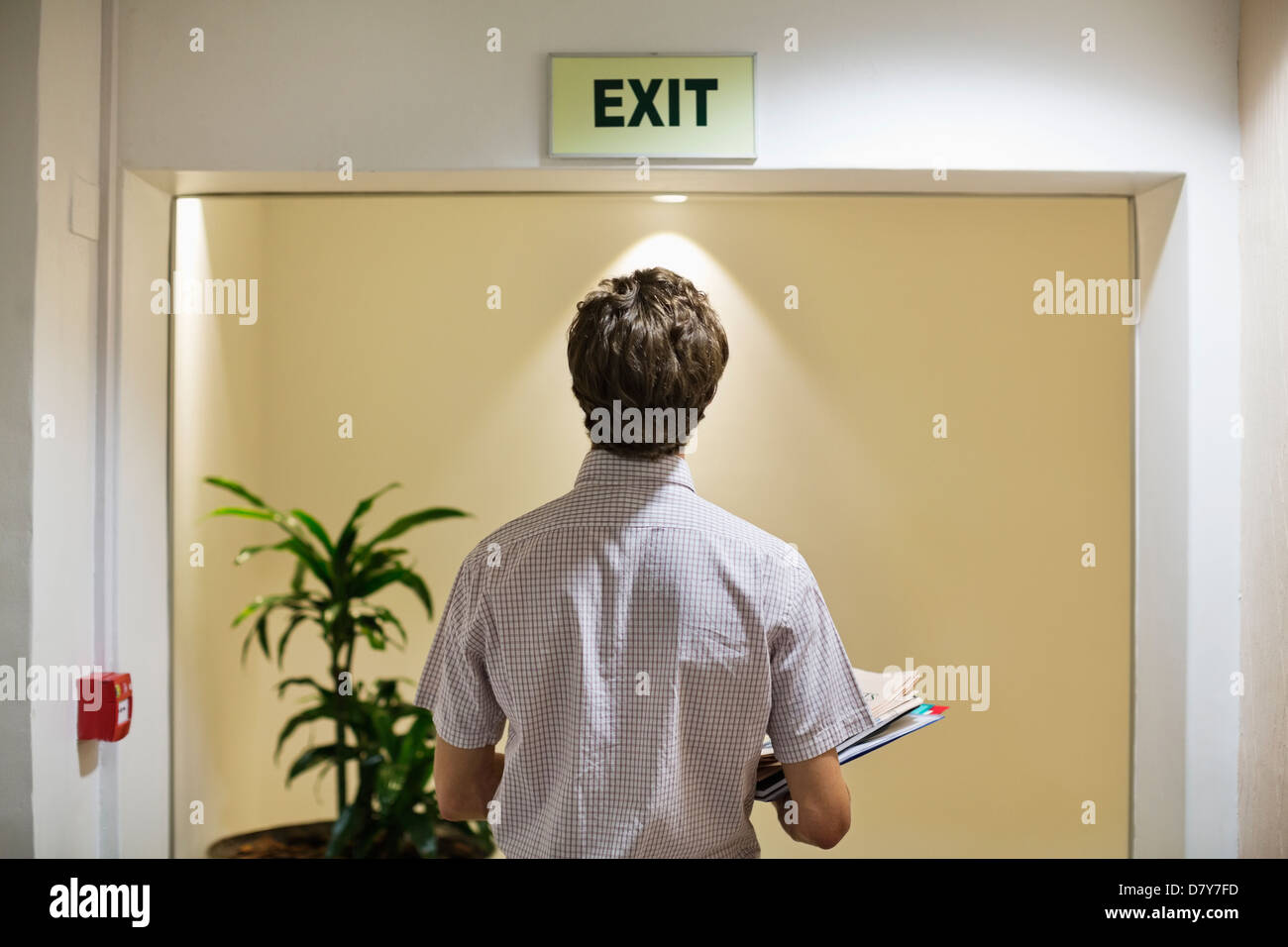 Businessman examining 'exit' sign in office - Stock Image