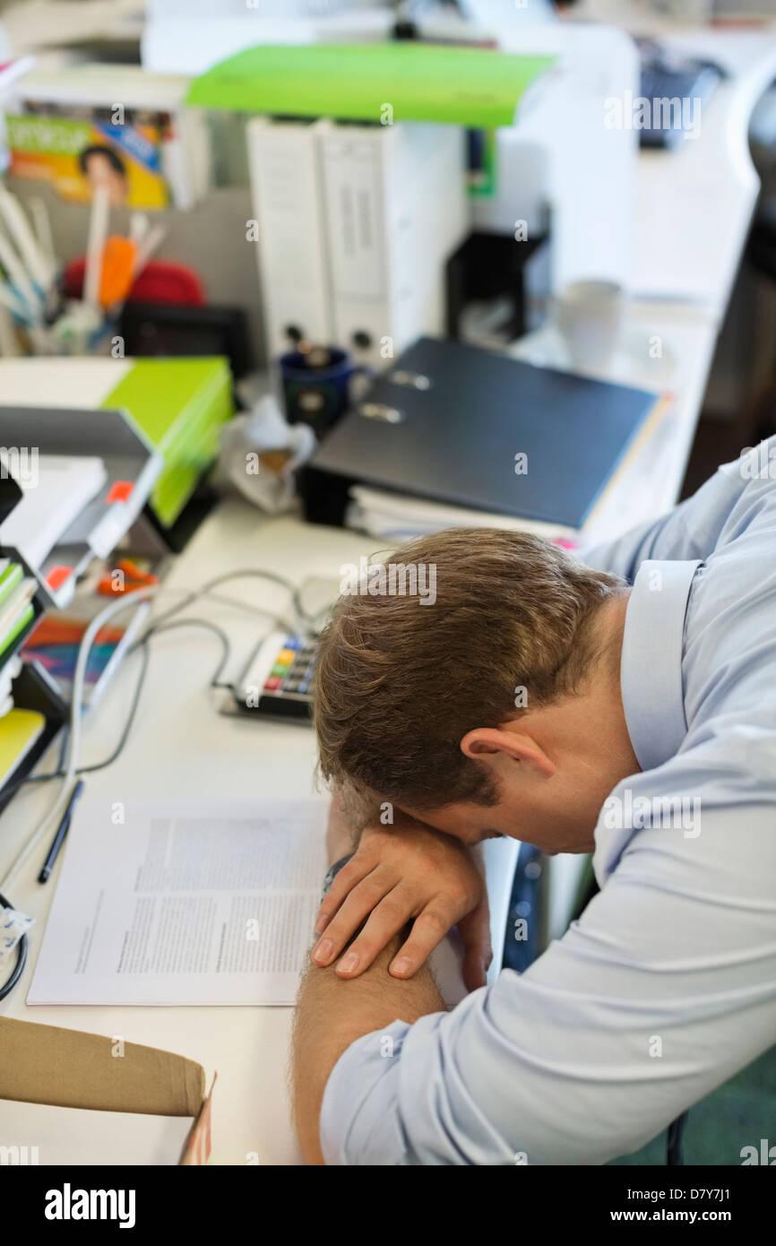 Businessman resting head on desk - Stock Image