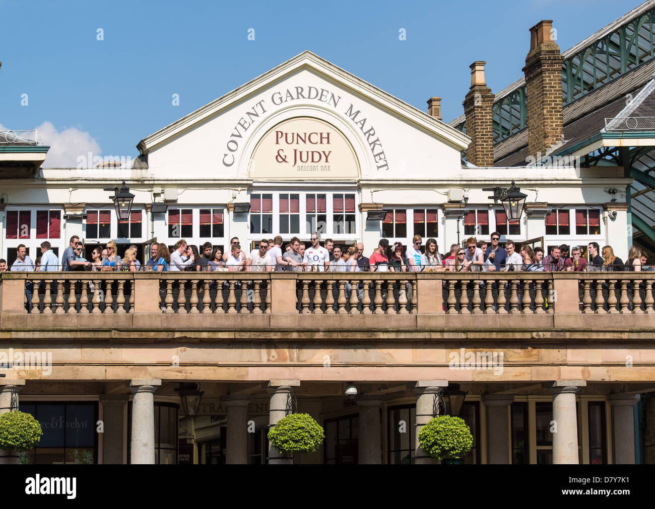 Balcony watchers with their drinks outside a pub look down on entertainers at Covent Garden. Stock Photo