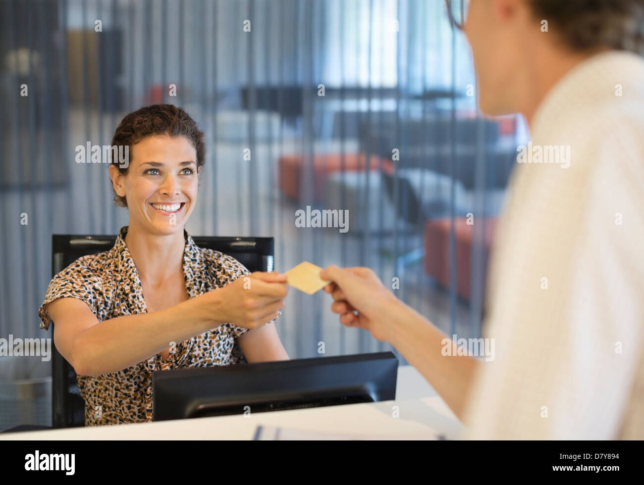 Businesswoman handing credit card to co-worker - Stock Image